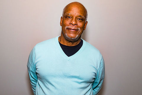 Stanley Nelson. Middle aged Black man with bald head and gray beard wearing a teal colored sweater and black Tee.