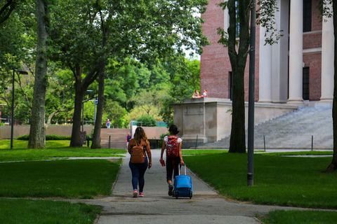 two people with luggage walk through a college campus.