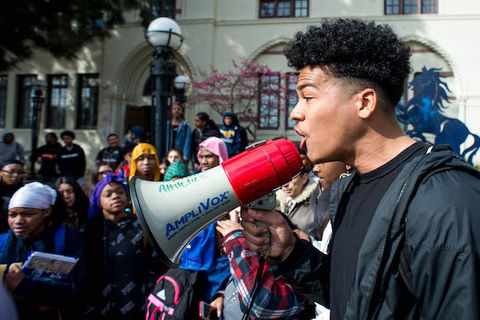 A Black student is holding a megaphone leading a crowd of students in protest.