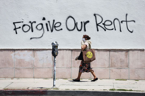 Unaffordable-Rent. Woman wearing mask walks passed spray painted message reading Forgive Our Rent.