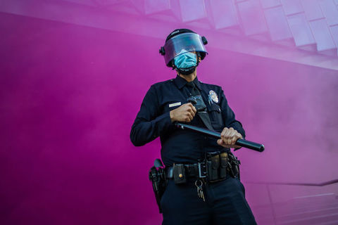 A uniformed police officer stands in front of a purple wall of smoke as they hold a baton and cover their face with a mask and shield.