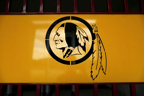 Washington DC NFL Team. Logo with yellow background and black ink of a stereotypical image of a Native American man wearing head feathers.