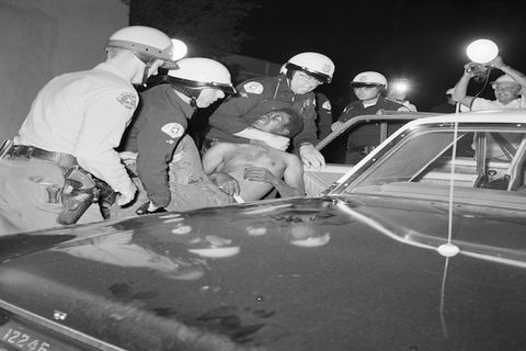 Black and white photograph of police officers forcing a Black man into a police car during second night of the Watts rebellion.