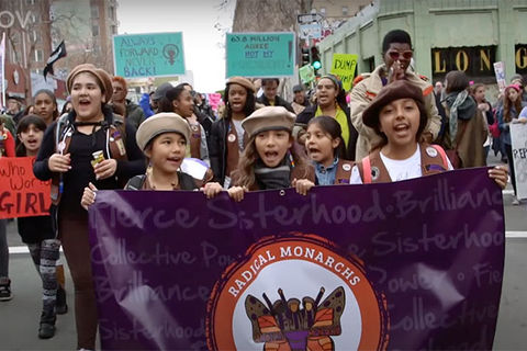 "We Are the Radical Monarchs. Three young girls of color wearing scouts caps and carrying a purple banner reading ""Radical Monarch"" march in a rally."