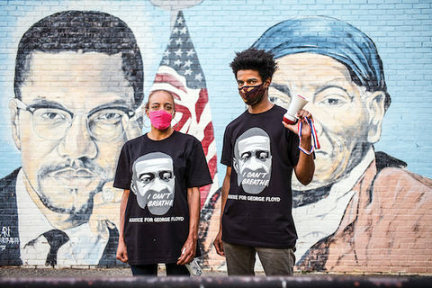 Two protesters stand in front of a painted mural of Malcolm X and Harriet Tubman.