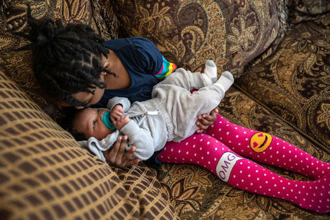 A little Black girl wearing pink stockings sits on a couch and kisses her newborn sibling on the head