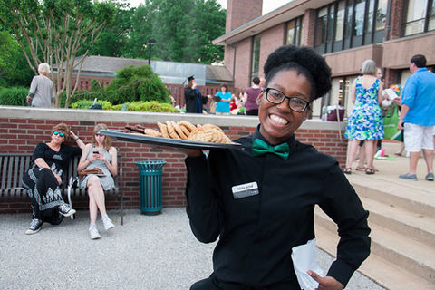 Black Waitress. Young Black woman with a dark Afro wearing a green bow tie and black shirt and pants holding a platter of cookies.