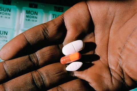 A Black hand palm facing up with three pills, a white oblong pill, an orange capsule and a white diamond shaped pill