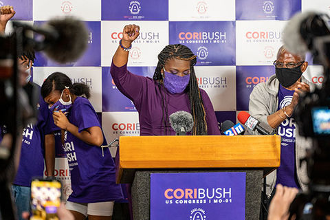 Cori Bush. Black woman wearing purple mask and top with a raised fist a podium surrounded by cameras.