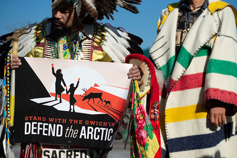Defend the Arctic Protest. Indigenous man standing next to someone in colorful stripped coat, holds sign reading: Defend the Arctic.