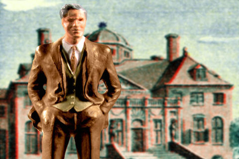 A figurine of a man in a suit stands in front of a backdrop of a house.