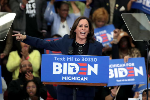 Kamala Harris stands at a podium with BIDEN written across the front.