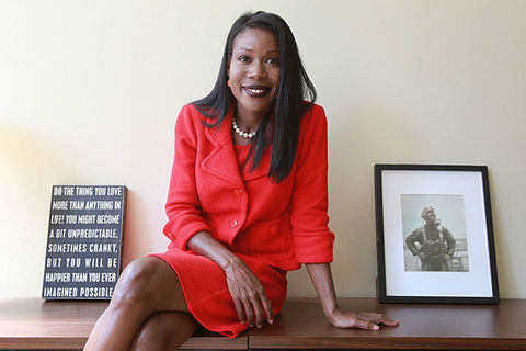Isabel Wilkerson. Black woman with long dark straight hair wearing red skirt suit sitting between two small pieces of desk art,