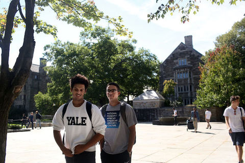 two students, one wearing a Yale sweatshirt, stand on the Yale campus.
