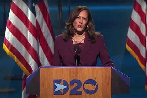 Kamala Harris. Black woman with shoulder length brown hair wearing maroon-colored suit standing in front of U.S. flags on stage.