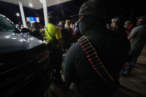 Kenosha Armed White Man. Back of white man standing in gas station wearing a hat, face covering and bullets across shoulder.