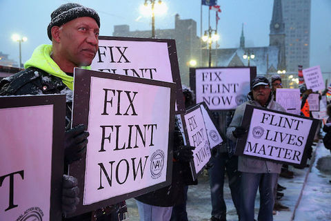 Protesters hold signs that read, Fix Flint Now and Flint Lives Matter