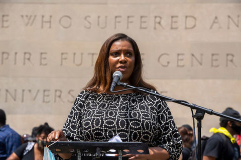 Black woman stands at a podium in front of a crowd and speaks into a microphone.