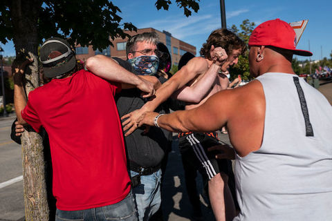 A small group of Black people and White people appear to be in a shoving match while standing outside.
