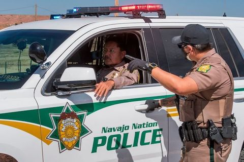 A uniformed officer stands and talks to another officer who sits inside a car that reads, Navajo Nation Police