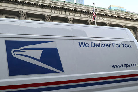 "USPS 2020. Side of postal service truck with words ""We Deliver For You"" in blue letters."