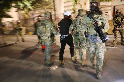 federal agents in riot gear arrest a citizen and walk away from the camera,