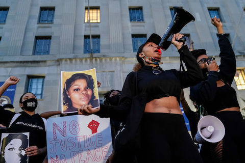 One woman holds a mega-phone in her hand as members of the surrounding crowd hold images of Breonna Taylor