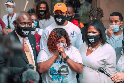 "A group of Black people stand around a microphone wearing face masks that read, ""Breonna Taylor."""
