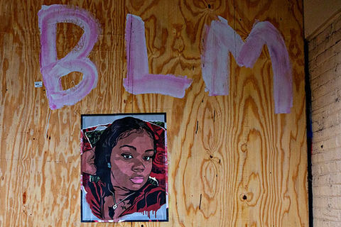 Breonna Taylor. Artwork of Black woman on a wooden board under the letters BLM.