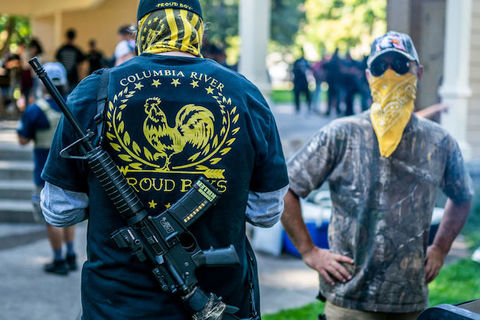white man with his back to the camera wears a jacket that reads Columbia River Proud Boys. Another white man facing the camera has a yellow bandana covering his mouth and nose.