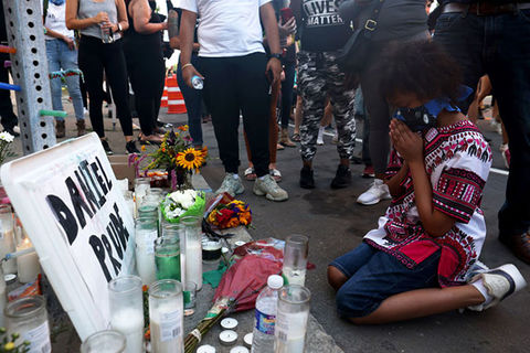 Daniel Prude. Young Black boy prayers on his knees on the ground at a makeshift memorial for Daniel Prude.