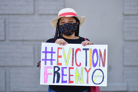Eviction Protest. Young woman wearing a hat and black face mask holds colorful sign reading: #EvictionFreeNYC