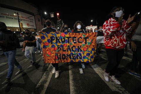 "People march at night, carrying a colorful banner saying ""Protect Black Women."""