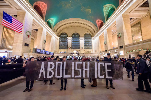 protesters hold a sign that reads, Abolish ICE
