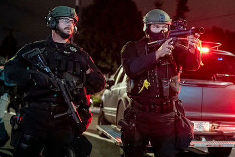 Police Violence. Two officers in uniform wearing helmets and carrying weapons while one is aiming the weapon.