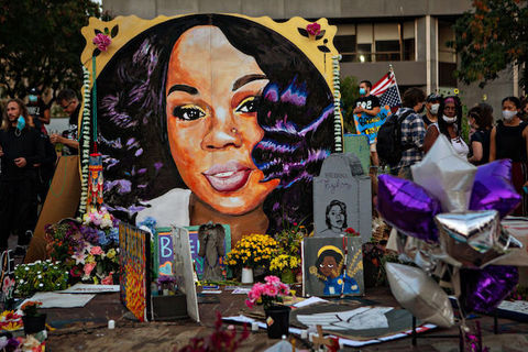 painting of Black woman with long black hair is surrounded by flowers and other tributes.