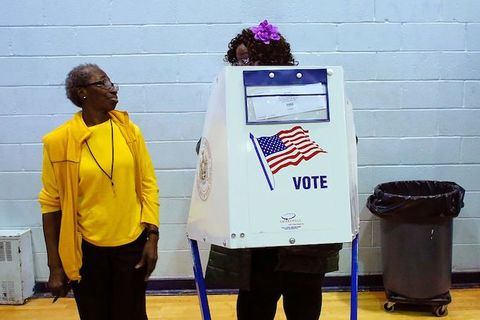 A Black woman wearing a yellow shirt and blazer speaks to another Black woman who wears a purple flower in her hair and stands behind a voting booth.