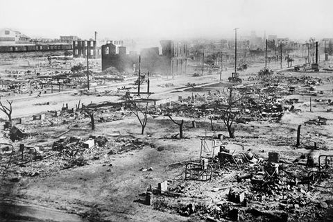 Tulsa. Black and white archival image of a burned down city of destroyed buildings and trees.