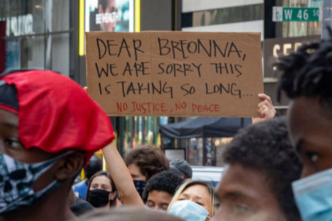 "Protester holds a sign that reads, ""dear Breonna, we're sorry this is taking so long. """