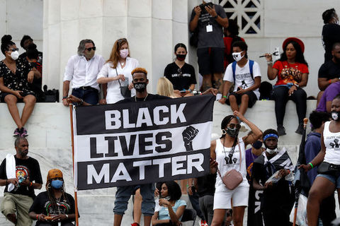 A large group of people are seated on a platform behind a Black man who stands and holds a large Black Lives Matter sign.