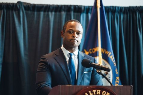 Black man with brown skin and close cropped hair in a blue suit standing at a lectern with a somber expression.