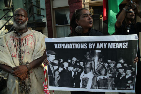 "Three Black people hold a large protest sign that reads ""Reparations By Any Means!"""