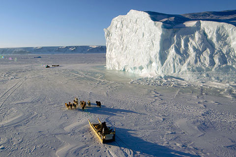 The Last Ice. Two dogsleds travel over sea ice and passed an iceberg.