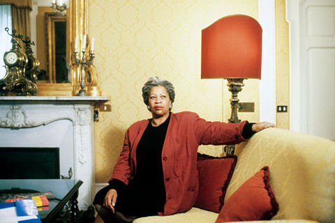 Toni Morrison. Black woman with long gray locs seated on a yellow sofa, wearing a black dress and red jacket.