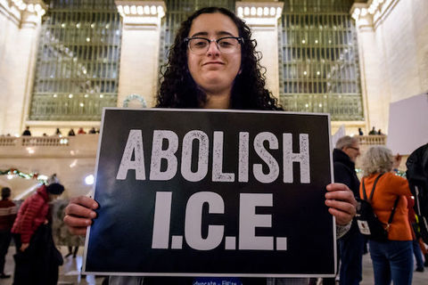A woman with dark curly hair holds a large sign that says, Abolish ICE