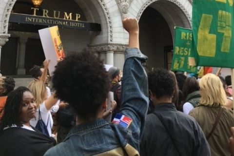 An assembled crowd of mostly women in front of Trump Hotel in Washington, D.C. One Black woman with a natural up-do, has her fist raised in the air.