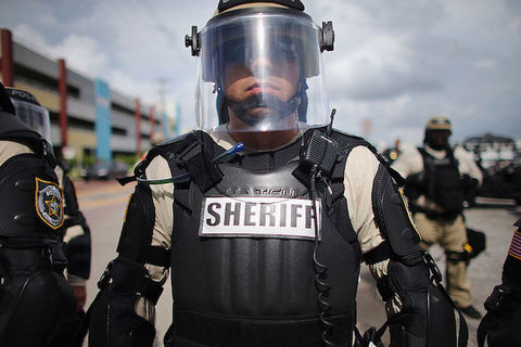 A sheriff in riot gear wears a clear face shield and has the word SHERIFF written in large letters across his bullet-proof vest.