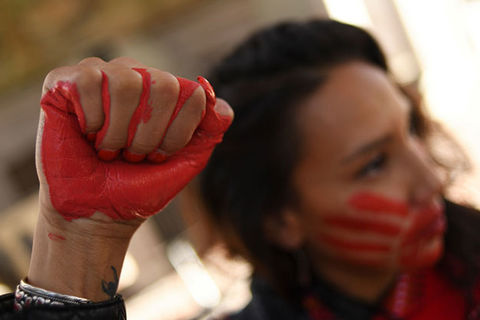 Indigenous Woman. Raised fist painted red with dark-haired woman with mouth covered in red hand in the background.