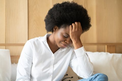 Black woman with an afro faces down with hand on forehead, looking depressed.