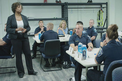 An African American woman in a suit teaches a class of uniformed police officers